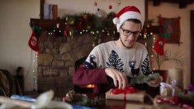 Gebaarde mens die en een boog op giften voor Nieuwjaar zitten binden dichtbij open haard Kerel die Kerstmishoed het verpakken hed stock footage