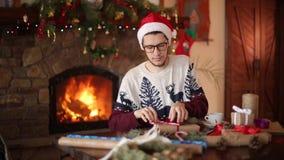 Gebaarde mens die en een boog op giften voor Nieuwjaar zitten binden dichtbij open haard Kerel die Kerstmishoed het verpakken hed stock videobeelden