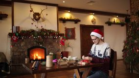 Gebaarde mens die en een boog op giften voor Nieuwjaar zitten binden dichtbij open haard Kerel die Kerstmishoed het verpakken hed stock video