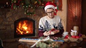 Gebaarde mens die en een boog op zitten binden giften dichtbij open haard Kerel die de verpakkende vakjes van de Kerstmishoed in  stock videobeelden