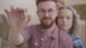 Gebaarde mens die in glazen met een meisje op een vage achtergrondholdingssleutels aan een nieuwe flat zit Portret van jongelui stock footage