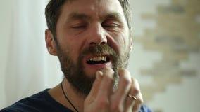 Gebaarde mens die ongezonde kost met groot plezier eten de kerel eet frieten Langzame Motie stock videobeelden