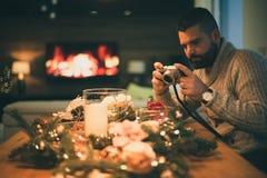Gebaarde mens die verfraaide Kerstmislijst fotograferen Stock Foto's