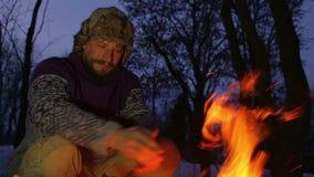 Gebaarde mens die zijn handen verwarmen door de brand in de winter De avondkampvuur van de toeristenmens stock videobeelden