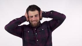 Gebaarde mens die zijn oren van een hevig lawaai behandelen stock video