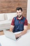 Gebaarde mens gebruikend laptop en thuis glimlachend bij camera Stock Foto's