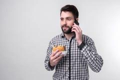 Gebaarde mens in geruit overhemd op een lichte achtergrond die een hamburger en een appel houden De kerel maakt snel de keus tuss stock afbeelding