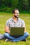 Gebaarde Mens in Glazen die aan Laptop werken stock fotografie