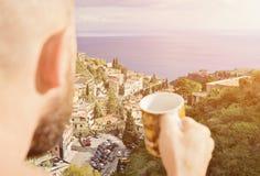 Gebaarde mens het drinken koffie in de vroege ochtend op het balkon stock fotografie