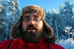 Gebaarde mens in het Russische uiterste van het de winterhoed verraste portret Stock Foto's