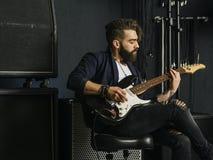 Gebaarde mens het spelen gitaar in een muziekstudio stock fotografie
