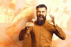 Gebaarde mens, lange baard Brutale Kaukasische gelukkige hipster die met snor in bruin overhemd alcoholisch rood geschoten houden stock afbeelding