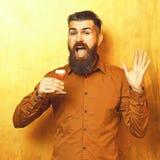 Gebaarde mens, lange baard Brutale Kaukasische het glimlachen gelukkige hipster die met snor in bruin overhemd alcoholisch rood s royalty-vrije stock fotografie