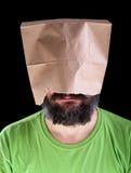 Gebaarde mens met document zak bij zijn het hoofd glimlachen Stock Afbeeldingen