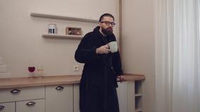 Gebaarde mens met kop thee stock videobeelden