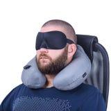 Gebaarde mens met slaapmasker en grijs reishoofdkussen op witte achtergrond Stock Fotografie