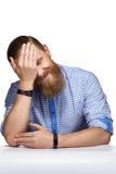 Gebaarde mens met snorzitting bij witte lijst stock afbeeldingen