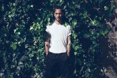 Gebaarde mens met tatoegering die lege witte t-shirt en zwarte jeans dragen De groene achtergrond van de tuinmuur horizontaal Mod Stock Foto