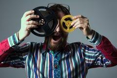 Gebaarde mens met twee 16mm filmspoel Royalty-vrije Stock Afbeeldingen