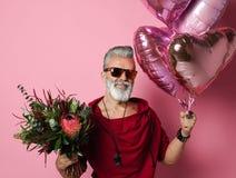 Gebaarde mens op middelbare leeftijd met ballons en bloemen stock afbeelding