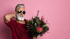 Gebaarde mens op middelbare leeftijd met ballons en bloemen stock foto's