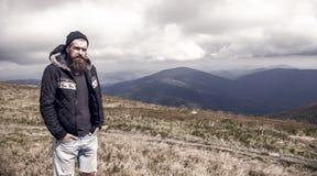 Gebaarde mens op winderige bergbovenkant op natuurlijke bewolkte hemel royalty-vrije stock foto
