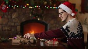 Gebaarde mens zitting en het binden boog op giften dichtbij open haard, die de verpakkende vakjes van de Kerstmishoed in document stock video
