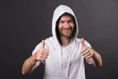 Gebaarde mensenglimlach met omhoog duimen Gelukkige mens met de kap van de baardslijtage Mannequin in hoodiet-shirt Actieve leven stock foto's