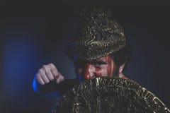 Gebaarde mensenstrijder met metaalhelm en schild, wild Viking Royalty-vrije Stock Afbeeldingen