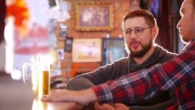 Gebaarde mensenzitting bij de bar Zijn vriend zit naast hem en zij schudden handen stock videobeelden