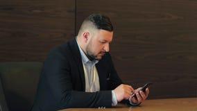 Gebaarde mensenzitting bij lijst en het gebruiken van mobiele telefoon in bedrijfsbureau stock footage