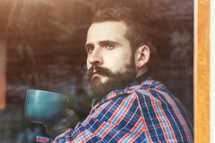 Gebaarde mensenzitting met kop van koffie stock foto's