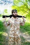 Gebaarde militair met een geweer in het hout Stock Afbeeldingen