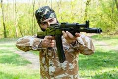 Gebaarde militair met een geweer in het hout Stock Foto
