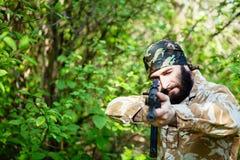 Gebaarde militair met een geweer in het hout Royalty-vrije Stock Afbeeldingen