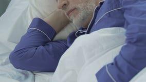 Gebaarde oude mens die op zijn partij en slaap, goede nachtrust liggen die energie herstellen stock footage