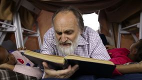 Gebaarde oude mens en kleinkinderen die een boek lezen stock video