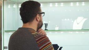 Gebaarde rijpe mens die juwelen huidig bij het winkelcomplex kiezen stock video