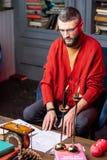 Gebaarde rijpe tovenaar die toekomst in de woonkamer voorspelt royalty-vrije stock foto's