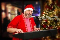 Gebaarde Santa Claus die digitale piano en het zingen spelen Royalty-vrije Stock Foto's