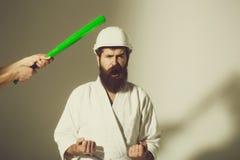Gebaarde schreeuwende karatemens in kimono, helm met honkbalknuppel stock foto