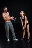Gebaarde sportman met sportfles en geïsoleerde de domoor van de sportvrouwholding Royalty-vrije Stock Fotografie
