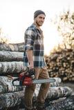 Gebaarde sterke houthakker die de greep in hand kettingzaag van het plaidoverhemd voor het werk aangaande zaagmolen dragen stock foto