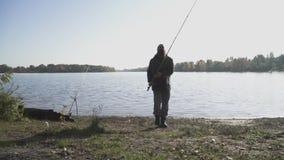 Gebaarde visserspas door de camera met hengel De man is bezig geweest met een hobby Rivier visserij Langzame Motie stock footage