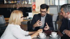 Gebaarde zakenman die met mannelijke en vrouwelijke partners in moderne koffie spreken stock footage