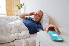 Gebaarde zakenman die slaperig na het ontvangen van vroege e-mail voelen stock fotografie