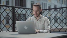 Gebaarde zekere jonge mensenzitting bij de lijst aangaande het terras voor laptop, het werken Concept freelance stock footage