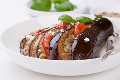 Gebackene Aubergine mit Tomaten, Käse und italienischen Kräutern Stockbild