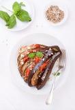 Gebackene Aubergine mit Tomaten, Käse und italienischen Kräutern Stockbilder