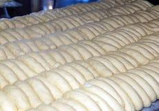 Gebackene Brote auf der Fertigungsstraße an der Bäckerei Lizenzfreies Stockbild